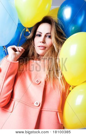blond woman in pink coat with balloons around her, studio shot