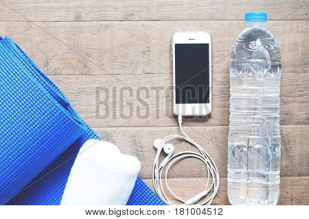 Flat lay of mobile phone with earphones water bottle towel and blue yoga mat on wood background. Healthy lifestyle and Yoga top view