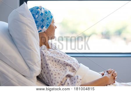 Young woman in bed suffering from cancer. Thoughtful woman battling with tumor looking out of window. Young patient with blue headscarf recovery in hospital on bed.