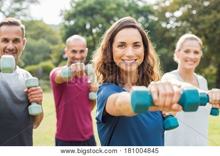 Mature people in training session of aerobics using dumbbells at park. Portrait of mature woman doing exercise with other people in background outdoor.