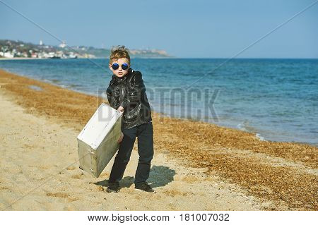 Boy with a suitcase on the beach. Young traveler and Explorer