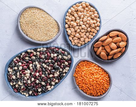 Vegetarian healthy protein sources on gray concrete background. Quinoa, chickpea, almond, red lentils, mixed bean as vegan sources of protein concept. Close up. Top view or flat lay.