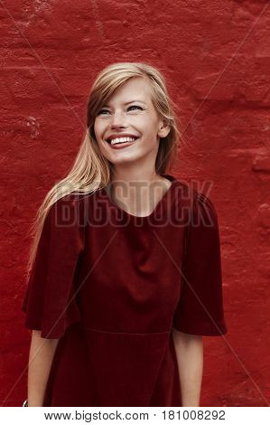 Stunning blond in red dress against red wall smiling