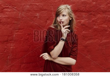Beautiful women with finger on lips on red wall