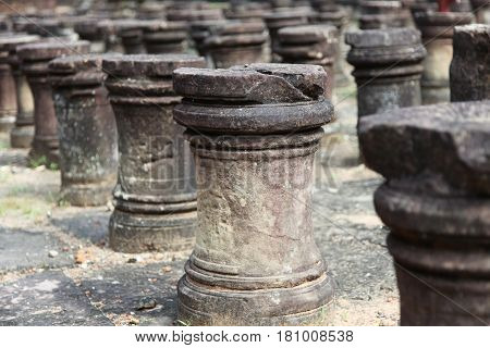 Ancient artfully carved from stone round columns sticking out of the ground.