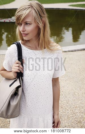 Shoulder bag girl in park looking away