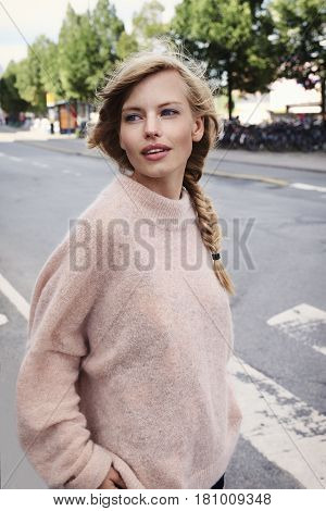 Beautiful girl in city looking over shoulder
