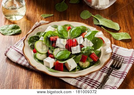 Fresh Spinach Salad With Feta, Cucumber And Red Paprika On A Plate.