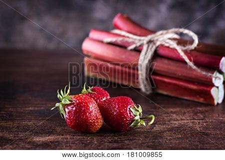 Strawberries And Rhubarb On Wooden Background.