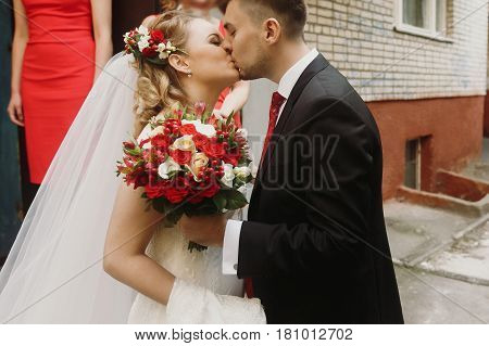 Handsome Groom In Black Suit With Wedding Bouquet Kissing Beautiful Blonde Bride In White Wedding Dr