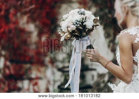 luxury wedding bouquet in bride hands golden leaves bouquet of roses and ribbons posing in park. space for text. sunny wedding reception. stylish bride in amazing expensive gown
