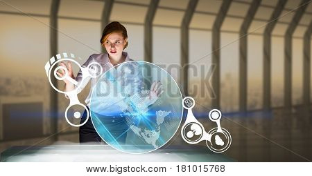 Digital composite of Businesswoman touching icons at futuristic desk in office