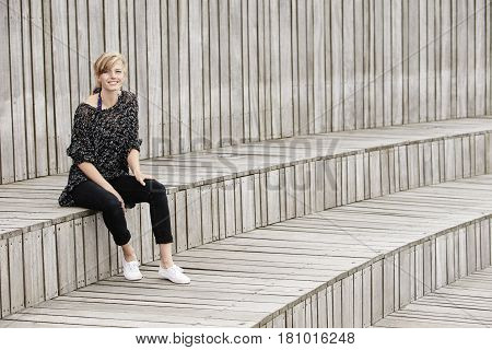 Beautiful woman smiling and sitting on wooden step