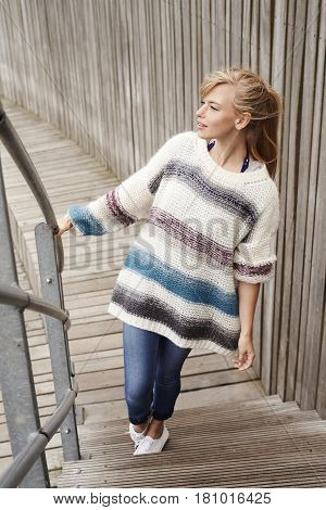 Beautiful young woman in sweater on wooden steps
