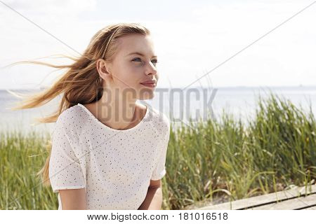 Windswept beautiful woman wearing summer dress  by sea