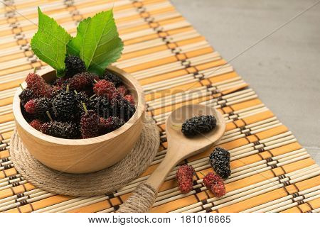 fresh mulberry fruit in bowl on wood background
