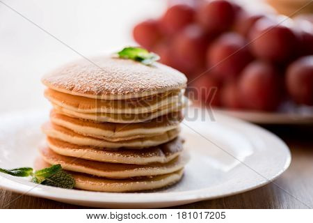 Tasty Pancakes With Mint And Powdered Sugar On White Plate