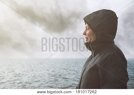 Optimistic female person enjoying morning sunlight at sea coastline on cold windy winter day anticipating unpredictable future