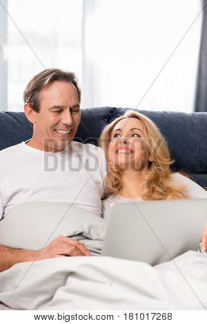Happy Middle Aged Couple Using Laptop And Lying On Bed At Home