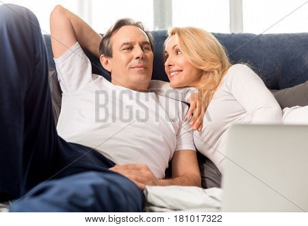 Happy Middle Aged Couple Looking At Each Other And Lying On Bed At Home