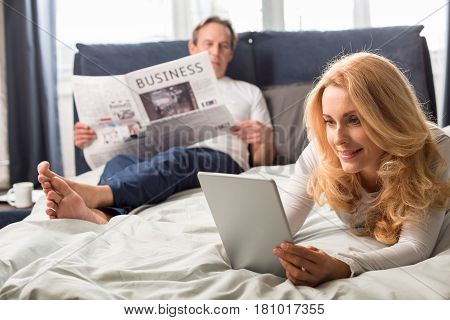 Middle Aged Woman Using Digital Tablet And Lying On Bed, Man Reading Newspaper Behind