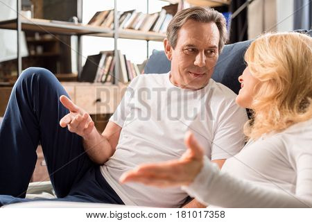 Happy Middle Aged Couple Talking And Lying On Bed At Home