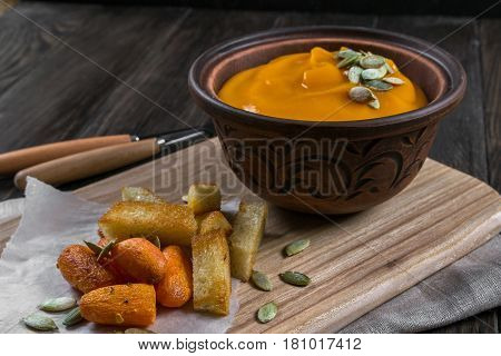 Pumpkin cream soup with snack fried croutons,baked carrots on dark wooden  table
