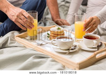 Cropped shot of couple having breakfast together in bed