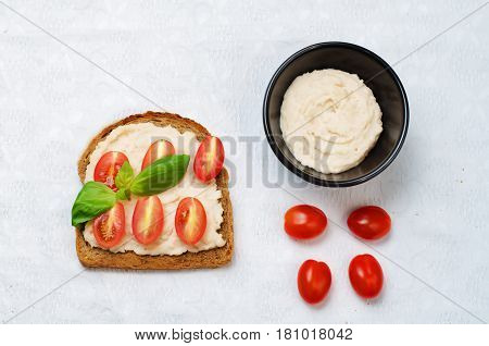 Healthy white bean hummus tomato rye breakfast sandwich.