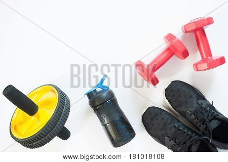 Flat lay of red dumbbells and sport equipment on white background. Sport accessories Sport equipments top view