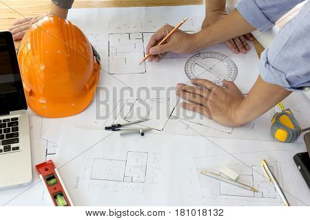 Interior Designer Discussing Data And Digital Tablet And Computer Laptop With Business Document And