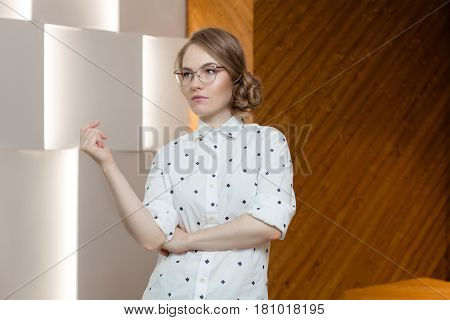 Young beautiful woman in glasses and elegant shirt posing on plain background.