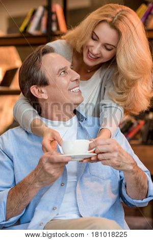 Smiling Blonde Woman Giving Tea Cup To Happy Mature Man