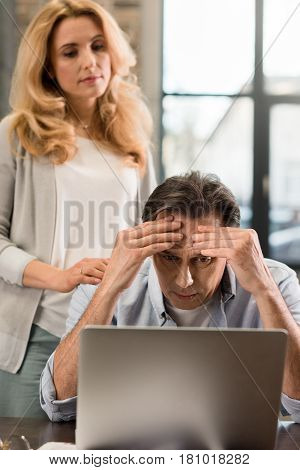 Blonde Middle Aged Woman Looking At Upset Husband Using Laptop At Home