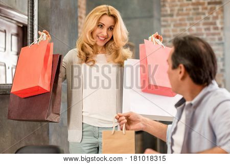 Happy Middle Aged Woman Holding Shopping Bags And Looking At Husband Sitting At Home