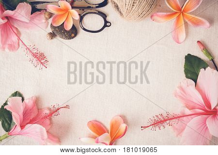 craft with Frangipani Plumeria Hibiscus flowers on linen copy space background selective focus toning