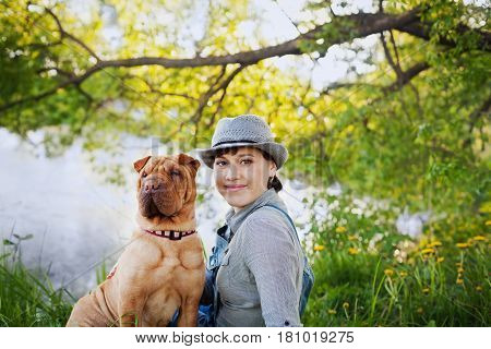 Happy young woman in a hat with dog Shar Pei sitting in the field in sunset light. True friends forever people with animals concept.