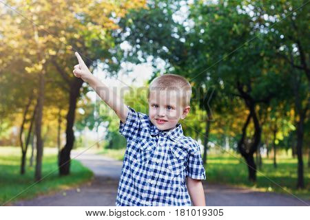 Сute and happy little smiling child boy showing a forefinger on the sun or the sky in beautiful autumn park.