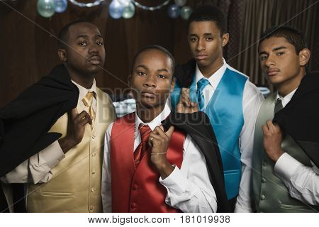 Multi-ethnic men holding suit jackets over shoulders