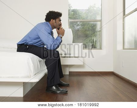 African businessman sitting on edge of bed