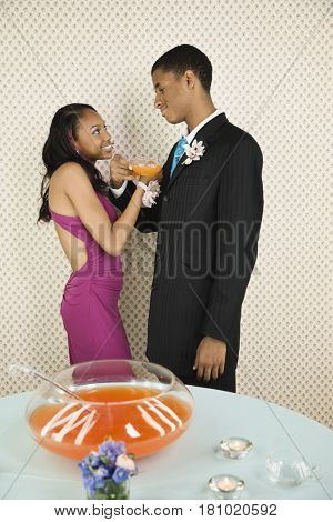 African teenaged couple drinking punch