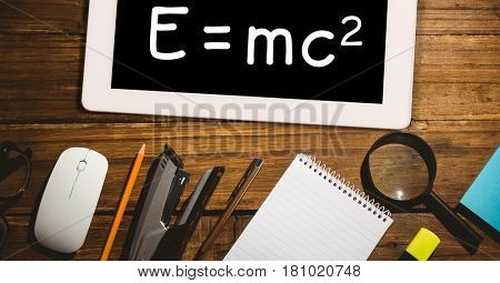 Digital composite of Directly above shot of formula in digital tablet with office supplies on wooden table
