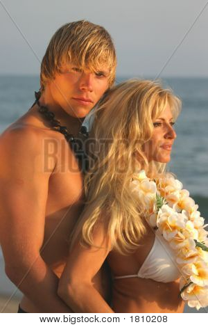 Cute Young Couple In Hawaiian Attire On The Beach At Sunset.