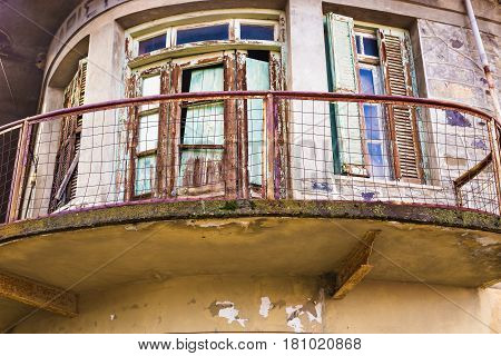 The balcony on the ruined building. Detail of a wall of an old almost ruined house with balconies