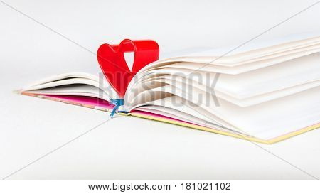 Red heart over diary book on white table. Side short, book slighly turned to left