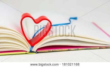 Red heart over diary book with bookmark on white table. Front short, bright colours
