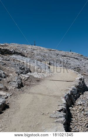 Stone Path among Barren Mountains Wooden Christian Cross and Worshippers in Italian Dolomites Alps in Summer Time