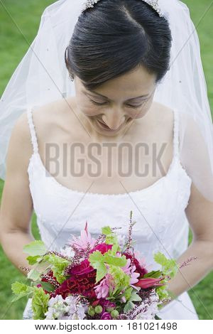 Asian bride looking at bouquet