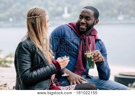 Romantic young couple holding glasses with cocktails and looking at each other while sitting outdoors