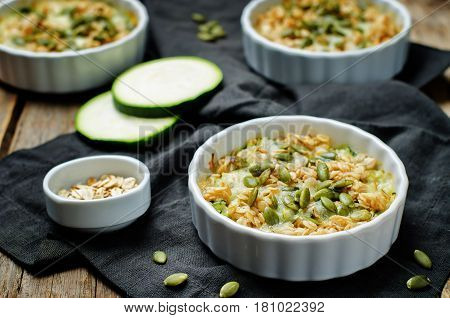cheese pepita oats zucchini casserole on wood background